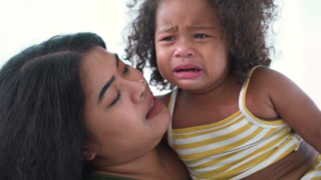 vidéos et rushes de la mère apaise sa petite fille pleurant - bébés filles