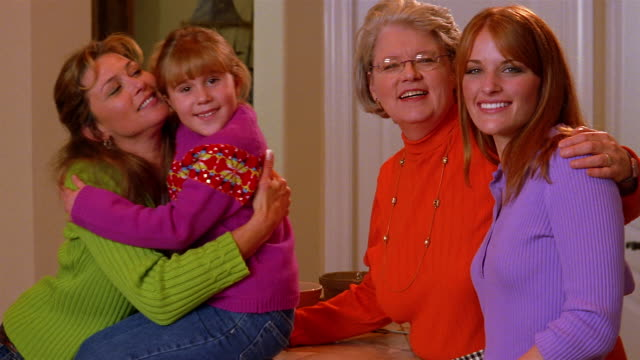A mother stands with her two grown daughters and her granddaughter.