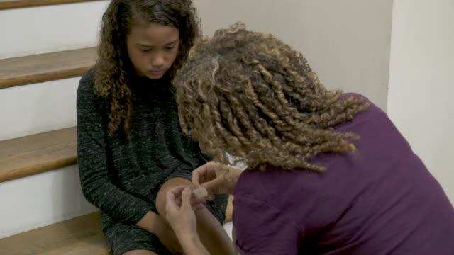 mother sticking plaster on daughters cut knee. - 絆創膏点の映像素材/bロール