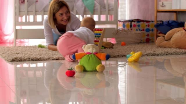 vídeos de stock, filmes e b-roll de mãe estimulando sua filhinha a rastejar com brinquedos - percepção sensorial