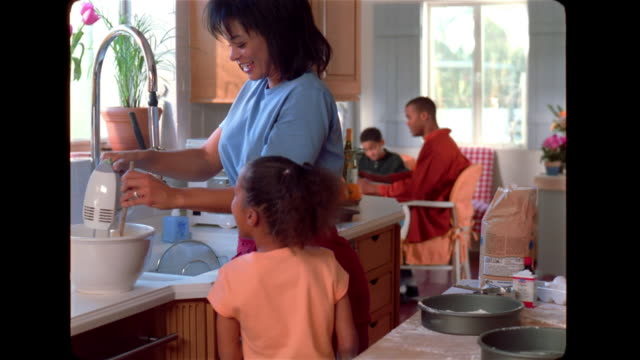 A mother stirs cake batter as her daughters watch.