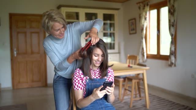 vídeos de stock, filmes e b-roll de mãe alisar o cabelo de sua filha - estilo de cabelo