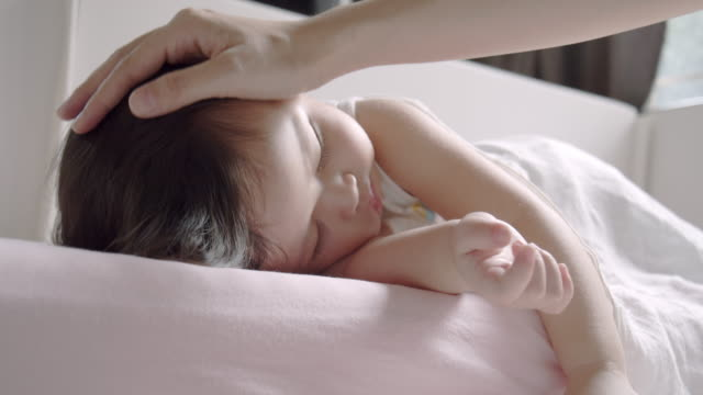 vídeos de stock e filmes b-roll de mother stroking head of sleeping baby daughter - acariciar