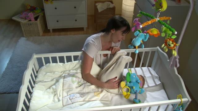 vídeos de stock, filmes e b-roll de grou hd: mãe de bebê stroking seu filme - pouca luz