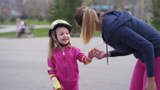 vídeos de stock e filmes b-roll de mother support her daughter while she learning how to skate - capacete de ciclismo