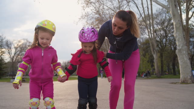 mother support her daughters while she learning how to skate - elbow pad stock videos & royalty-free footage