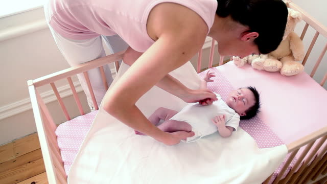 mother swaddling newborn baby in crib - baby blanket stock videos and b-roll footage