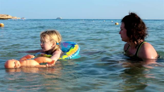 vídeos de stock e filmes b-roll de mother swims with her daughter in the sea. - molhado