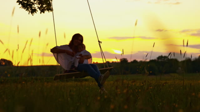 SLO MO Mother swinging with her baby girl at sunset
