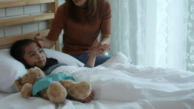 vídeos de stock, filmes e b-roll de mãe cuida dela garota paciente - termômetro