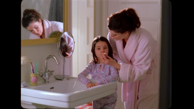 vídeos de stock, filmes e b-roll de a mother takes her daughter's temperature. - termômetro
