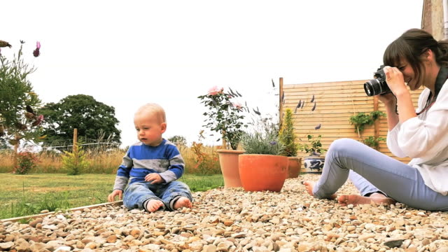 Mother takes pictures of baby in garden on dslr