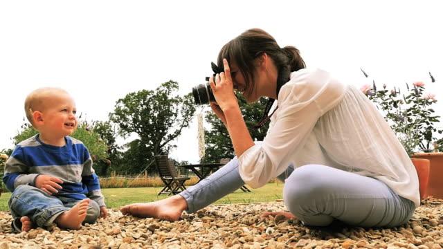 mother takes pictures of baby in garden on dslr - デジタル一眼レフカメラ点の映像素材/bロール