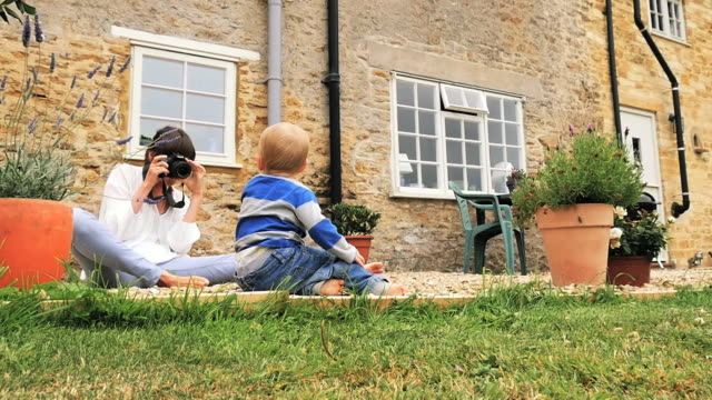 mother takes pictures of baby in garden on dslr - digital camera stock videos & royalty-free footage