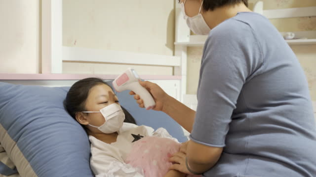 vídeos de stock e filmes b-roll de mother takes temperature of sick daughter - cold temperature