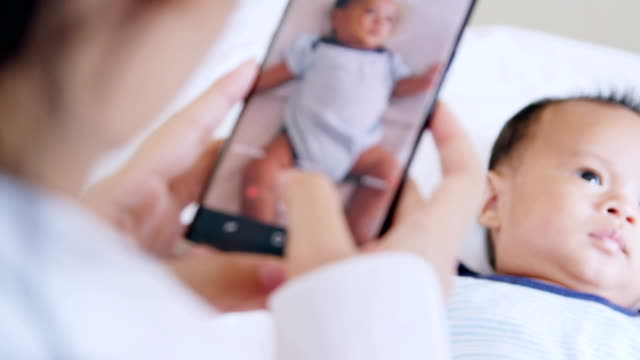 mother taking a picture of her cute little baby boy - photographing stock videos and b-roll footage