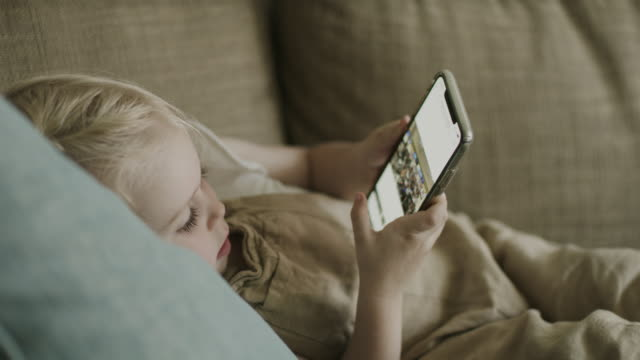 mother taking cell phone from daughter laying on sofa / american fork, utah, united states - arts culture and entertainment stock-videos und b-roll-filmmaterial