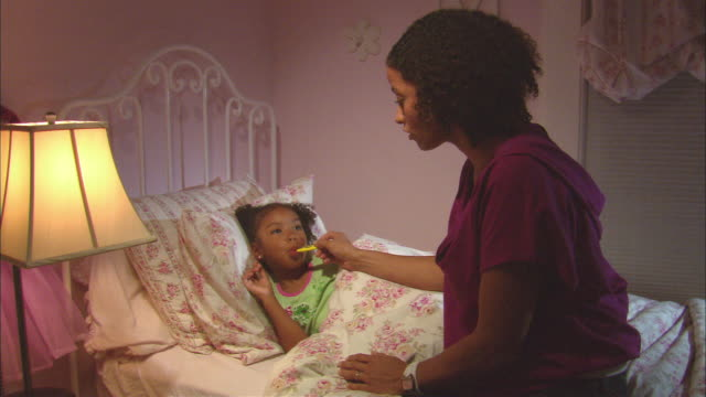 MS, mother taking daughter's (4-5) temperature in bed, Westfield, New Jersey, USA