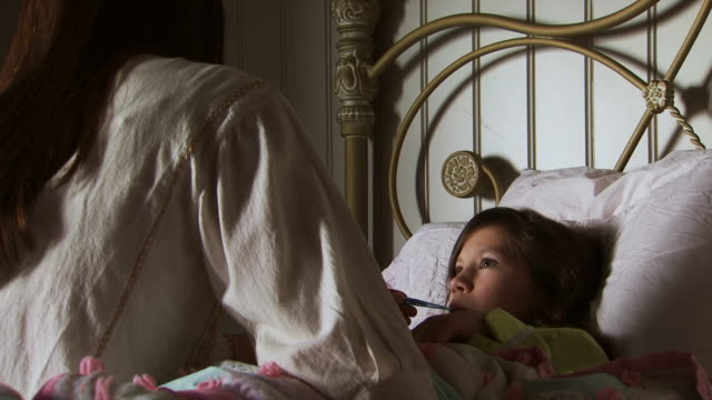 mother taking daughter's temperature with thermometer in bed - fieber stock-videos und b-roll-filmmaterial