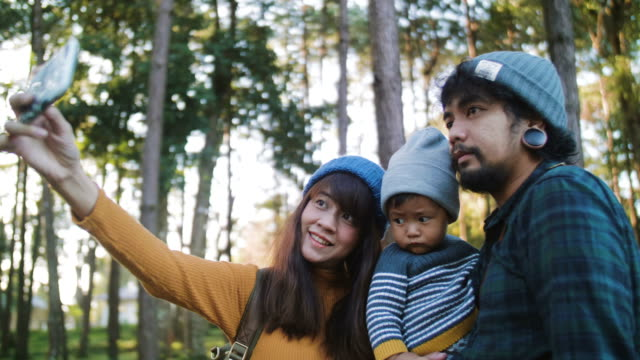 Mother taking family selfie in a forest with smartphone