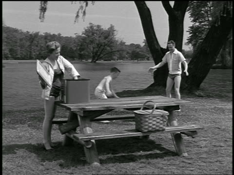b/w 1954 mother taking milk from cooler at picnic table as father + son play with beach ball by lake - cool box stock videos and b-roll footage