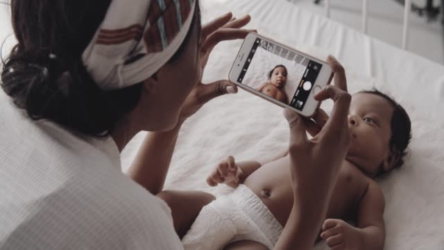 mother taking photo of newborn on bed - non us film location stock videos & royalty-free footage
