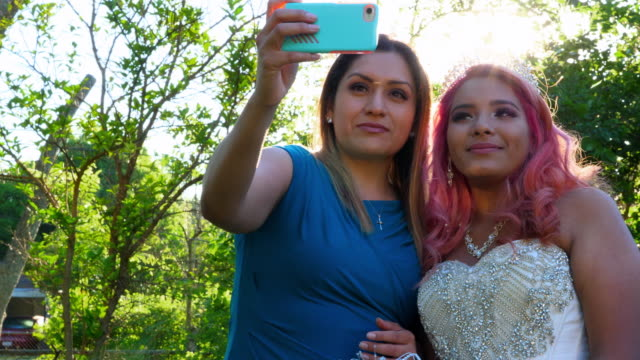 ms mother taking selfie with daughter dressed in quinceanera gown in backyard - crown headwear stock videos and b-roll footage