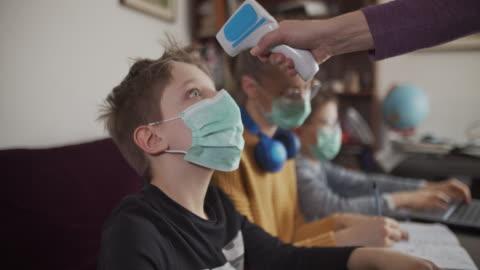stockvideo's en b-roll-footage met moeder die temperatuur van jonge geitjes neemt die aan online schoolklasse bijwonen. - young men