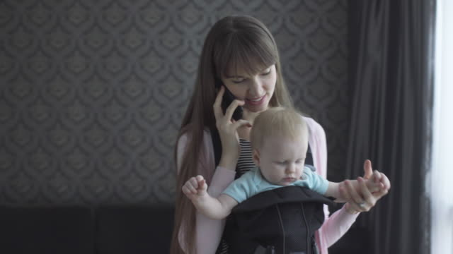 ms mother talking on phone while holding baby in a baby carrier - brown hair stock videos & royalty-free footage