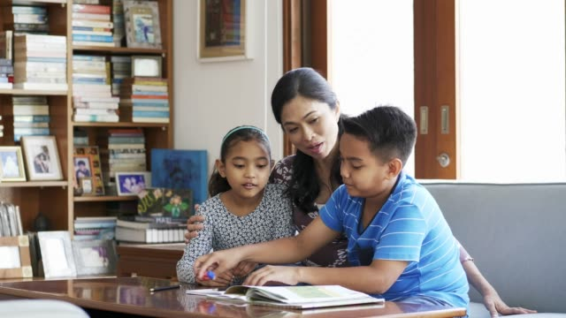 mother talking to kids while assisting in homework - guidance stock videos & royalty-free footage