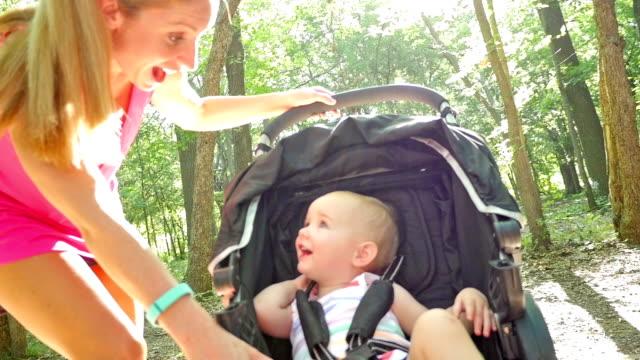 Mutter und Kleinkind Tochter reden, wie Sie drückt ihr in Kinderwagen im park