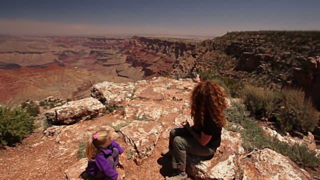 mother talks to her young daughter on the rim of the grand canyon and points over edge - 見渡す点の映像素材/bロール