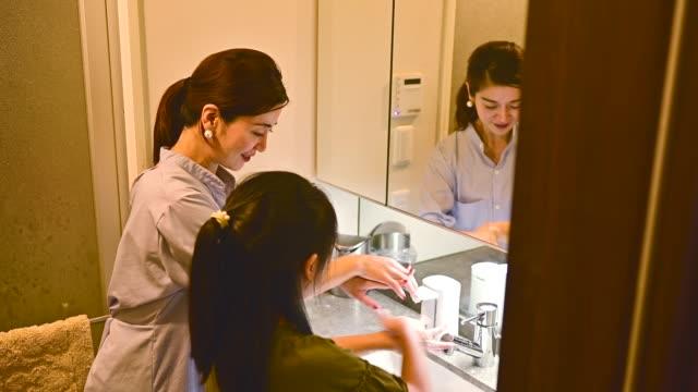 母は娘に手洗いを教えている。 - お手洗い点の映像素材/bロール