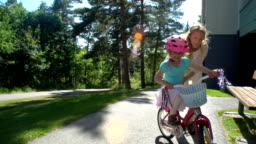 Mother Teaches her Daughter to Ride a Bicycle