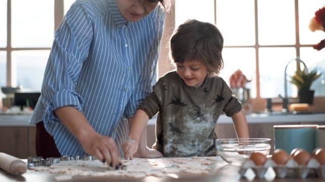 vídeos de stock e filmes b-roll de mother teaches little boy how to make gingerbread cookies - fazer