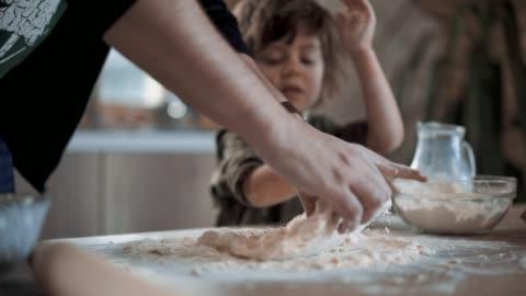 vidéos et rushes de mère enseigne petit garçon à faire de la pâte pour biscuits de pain d'épice - 4 5 ans