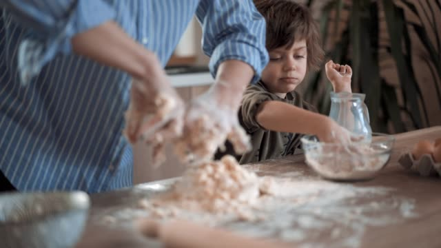 mother teaches little boy to make dough for gingerbread cookies - buttermilk biscuit stock videos & royalty-free footage