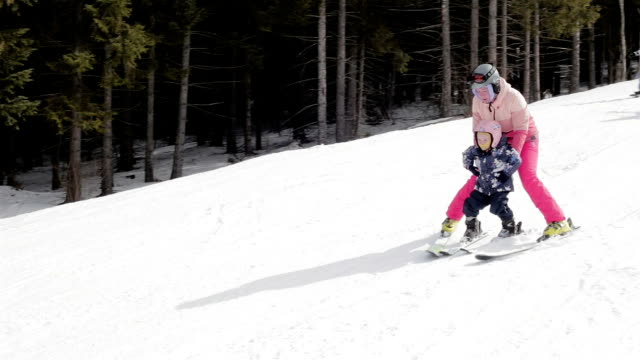 mother teaches the child to ski. - stazione sciistica video stock e b–roll
