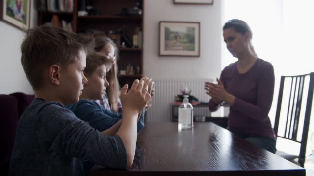 mutter lehrt kinder, hände mit antibakteriellem handgel zu desingieren - vier personen stock-videos und b-roll-filmmaterial