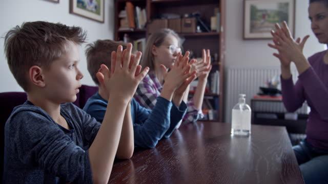 mutter lehrt kinder, hände mit antibakteriellem handgel zu desingieren - hygiene stock-videos und b-roll-filmmaterial