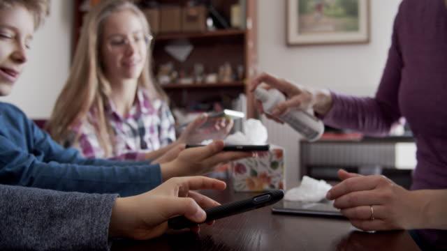 vidéos et rushes de mère enseignant aux enfants à assainir les smartphones avec le spray antibactérien - virus