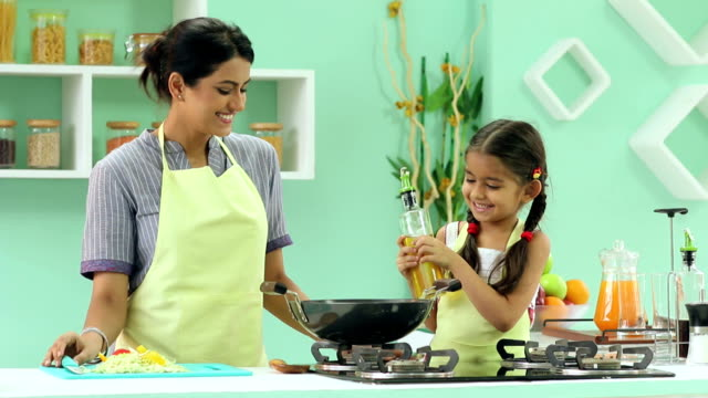 mother teaching cooking to her daughter, delhi, india - daughter stock videos & royalty-free footage
