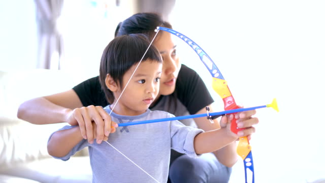 mother teaching cute son to archery. - bow and arrow stock videos and b-roll footage