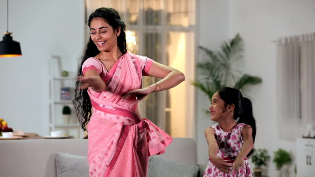 Mother teaching dance to her daughter, Delhi, India