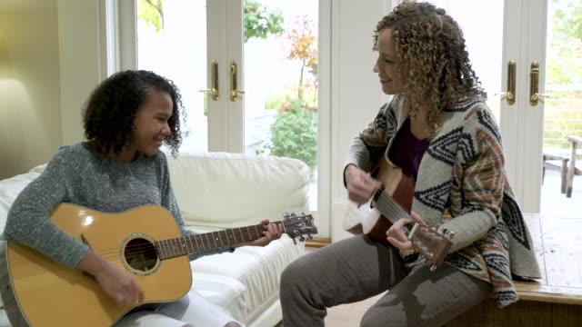 mother teaching daughter guitar. - akkord stock-videos und b-roll-filmmaterial