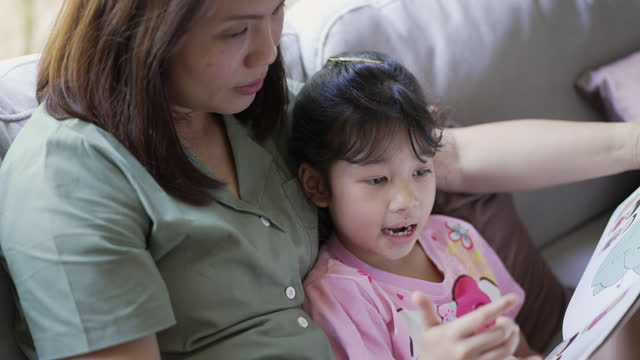 mother teaching daughter reading a book together in living room at home - childhood stock videos & royalty-free footage