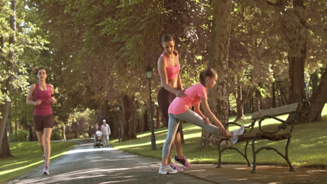 ds mother teaching daughter stretching exercises in the park - vest stock videos and b-roll footage