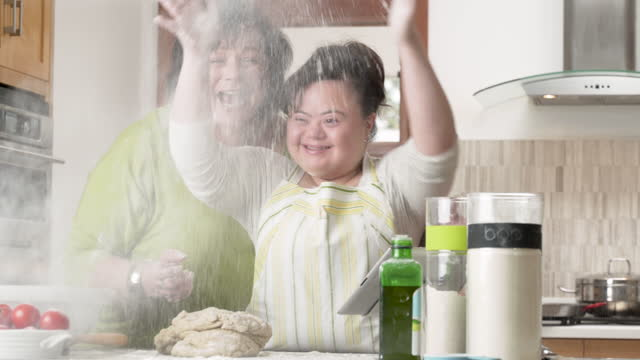 mother teaching daughter to bake in the kitchen - sindrome di down video stock e b–roll
