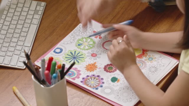 mother teaching daughter to color in coloring page - kunst und kunsthandwerk stock-videos und b-roll-filmmaterial