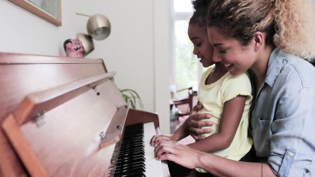 vidéos et rushes de mother teaching daughter to play the piano - instrument de musique